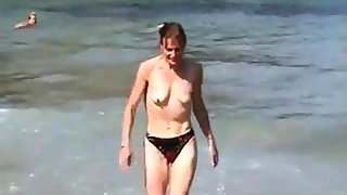 girl topless on beach with small empty saggy Bristols